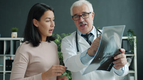 Patient and doctor looking at X-ray image talking indoors in office in hospital Live Action