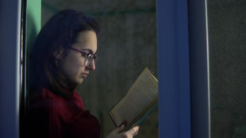 A young woman is sitting at home with a book in her hands. A girl sits on a Live Action