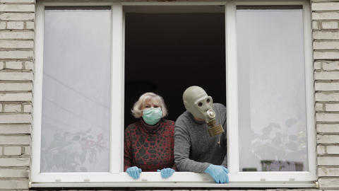 Old grandparents stay at window isolated at home on quarantine. Coronavirus Live Action
