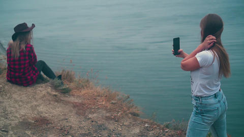 The background of the sea, one girl photographs another girl on a smartphone Live Action