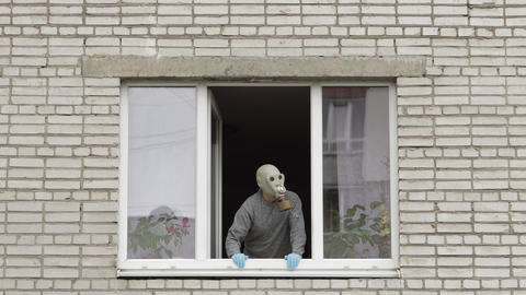 Old man in gas mask stay at window isolated at home on quarantine. Coronavirus Live Action