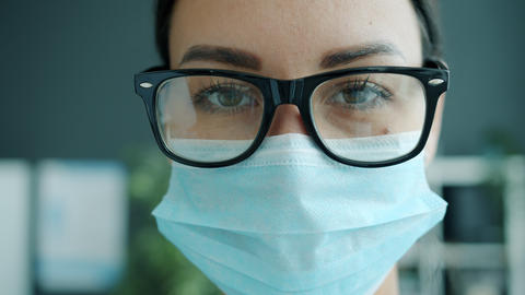 Slow motion close-up portrait of serious lady medic in mask and glasses in Live Action