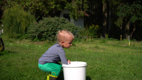 young wet child boy playing with plastic watering can and big bucket Live Action