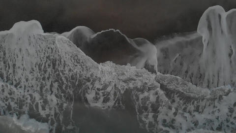 Ocean aerial top view at twilight with shoreline hit by raging waves crashing on the dark sand in Live Action
