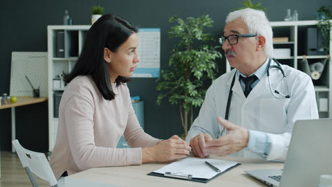 Caring doctor talking to young woman holding hand expressing support and care in Live Action