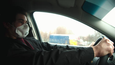 Young man in protective white mask driving a car in bad weather Live Action
