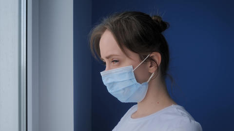 Self isolation: woman with face mask suffering from coughing at home: close up Live Action
