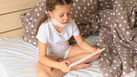 Little girl in a respiratory mask sits in quarantine in tablet Live Action