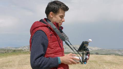 Man controlling quadrocopter flight, professional cameraman filming aerial video Footage