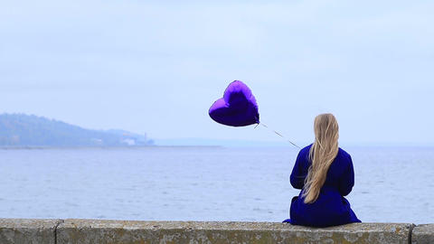 Upset young woman holding violet heart balloon Footage