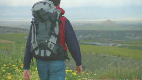 Young man wearing camping outfit and rucksack looking at mountains, traveling Footage