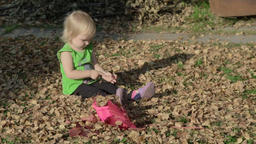 Cute baby girl playing with leaves in autumn Footage