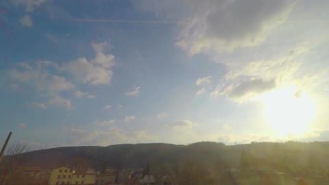 View through train window, sunny blue sky with clouds, trees, hills on horizon Footage