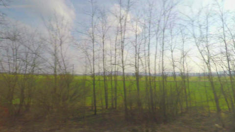 View from train moving at high speed, passing green fields, railroad crossings Footage