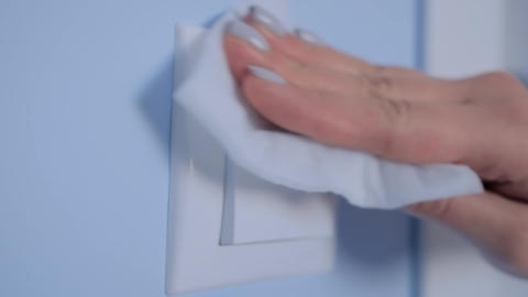 Slow motion: woman cleaning light switch with wet wipe - disinfection concept Live Action