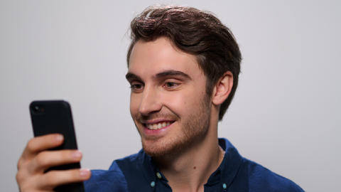 Man using mobile phone on white background. Guy browsing internet on cellphone Live Action