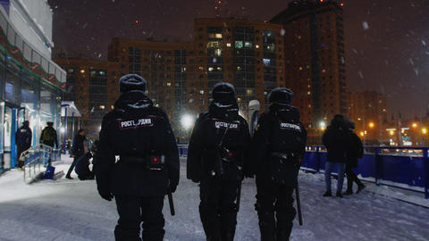policemen with batons walk past stadium in winter evening Live Action