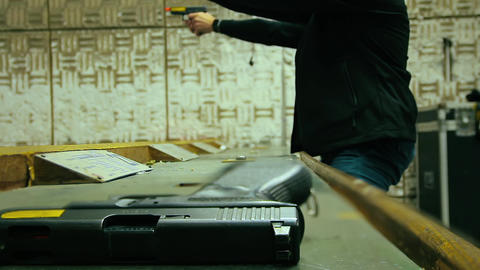 Cinemagraph of two unrecognizable men shoot with 9mm pistol in shooting range Live Action