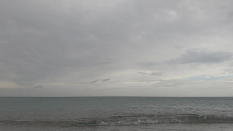 Suggestive time lapse of the flat sea with cloudy grey sky in flat color Live Action