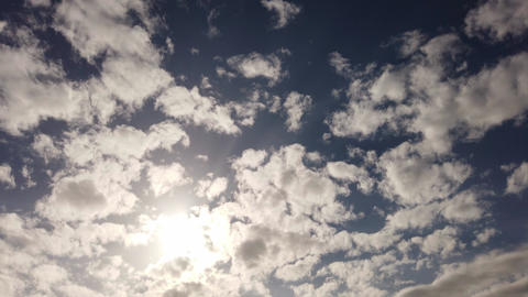 Awesome summer sky timelapse with sun and scenic altocumulus clouds flies in a blue sky Live Action