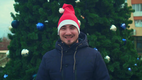 Young man with beard in santa hat on christmas tree background. Happy man Live Action