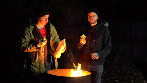 Two homeless young men stand by the fire and eat apples. Men stand at night near Live Action