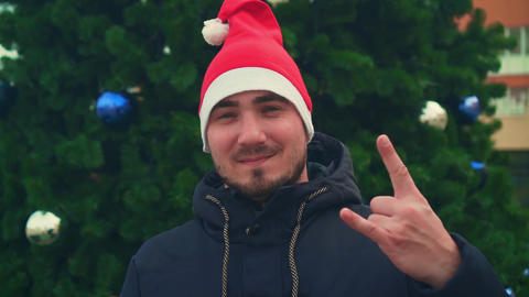 Man in santa hat showing like sign, rock sign, communication concept Live Action