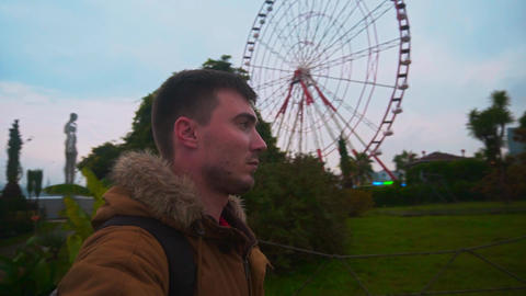 Selfie video shooting. Video blogger on a background of a ferris wheel, the sea Live Action
