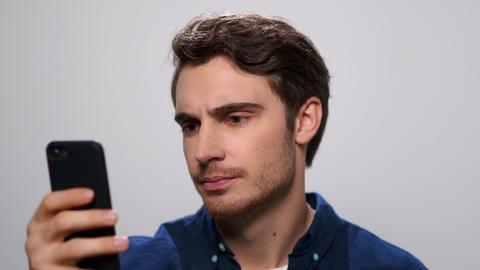 Upset man reading bad news on smartphone. Sad guy using phone in studio Live Action