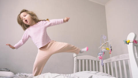 Happy childhood for child girl who jumping on the bed Live Action