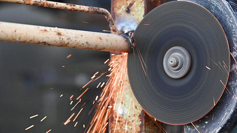 Construction worker using Angle Grinder Cutting Metal at construction site Live Action