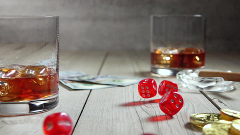 Whiskey in Highballs on a Wooden Table and Dice. Slow Motion Live Action