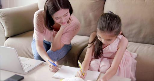 mother working at home and help daughter doing home work Live Action