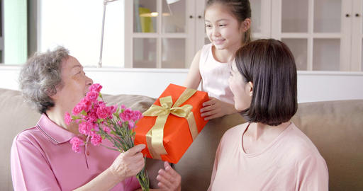Happy mother's day . Child and mother congratulating grandmother giving her flowers and gift box Live Action