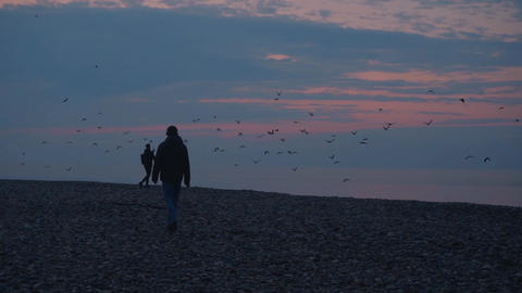 Two silhouettes against the backdrop of the sea and sunset. A male silhouette Live Action