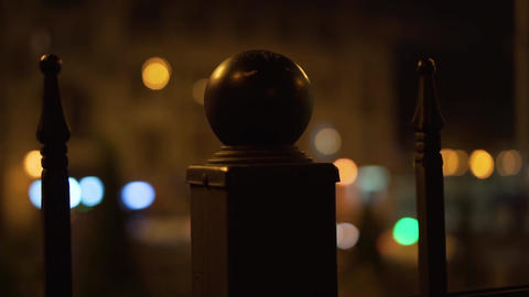 Round pillar, night city. Glowing lights behind Live Action