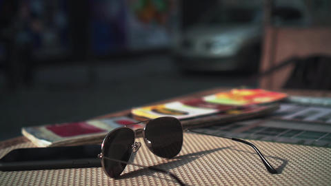 Sunglasses and a smartphone on the table of a summer street restaurant. In the Live Action
