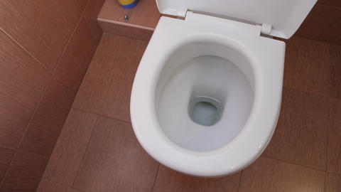 Water flushes the white toilet Live Action