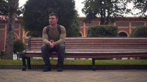 A man is sitting alone on a bench in an empty city and is listening to music on Live Action