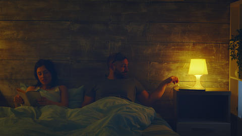 Woman reading a book in bed at night lamp Live Action