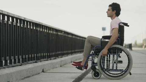 Thoughtful young man sitting on wheelchair. Sad disabled on wheelchair outside Live Action
