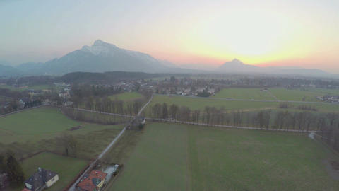 Beautiful mountains hiding sun on horizon, green farming fields, amazing sunrise Footage