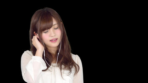 Young Japanese woman listening the music by earphone / iphone 4 Footage