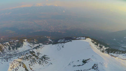 Aerial panorama of big city at mountain bottom in Austrian Alps, high snowy peak Footage