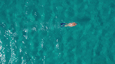 Aerial - Top down view of a woman snorkeling in a deep water with white sand Footage