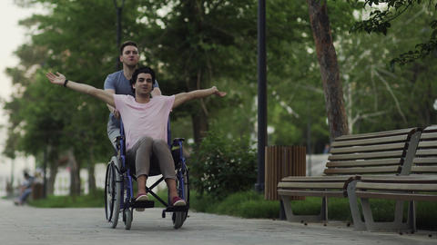 Happy disabled man in a wheelchair with happy young man running at the city park Live Action