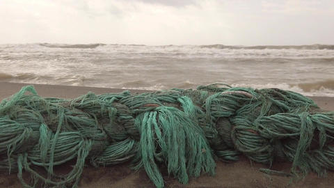 Plastic waste in the ocean, nature gives back man's damage with the remains of a plastic net spewed Live Action