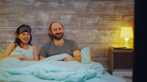Amused couple watching TV in bedroom Live Action