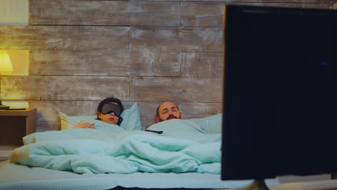 Couple in bedroom falling asleep in fron of tv Live Action