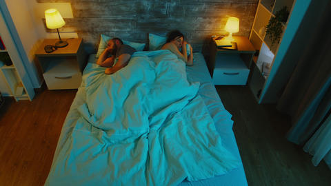 Top view of young couple under the sheets can't sleep Live Action
